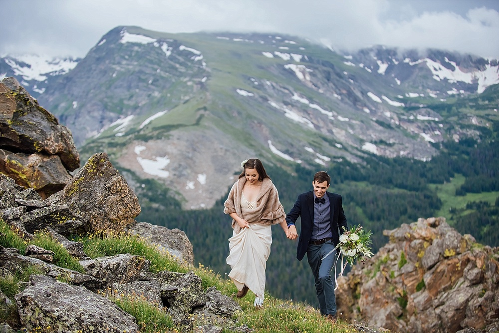 I love this cute shot of the bride and groom hiking around Rocky Mountain National Park near Trail Ridge Road for their epic Estes Park Elopement. Photo by Maddie Mae Photography.