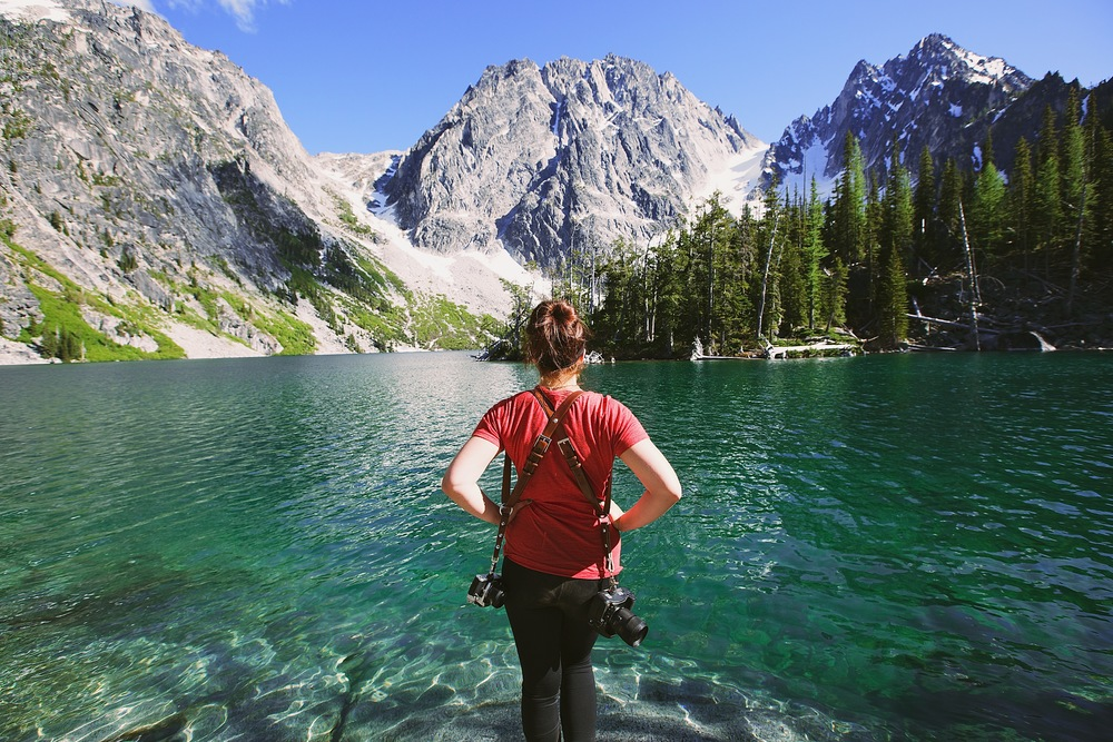 This is a photo of maddie mae photography after a 9 mile hike up to a mountain lake. She is a mountain wedding photographer based out of Colorado.