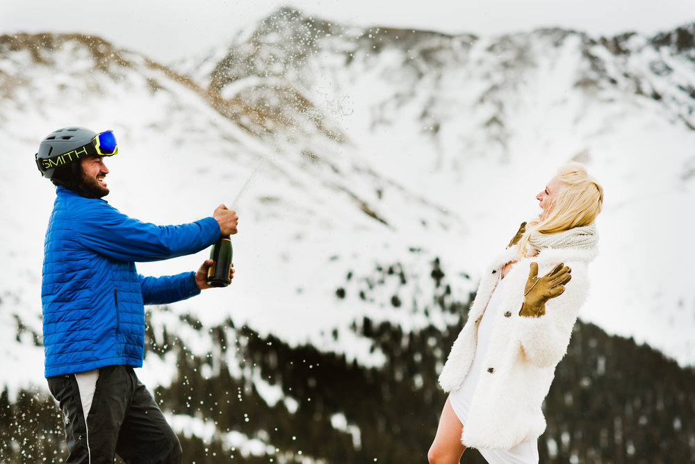 Pop! Champagne flying everywhere, snow falling around them... these newlyweds did it right! | Adventurous wedding photography by Maddie Mae