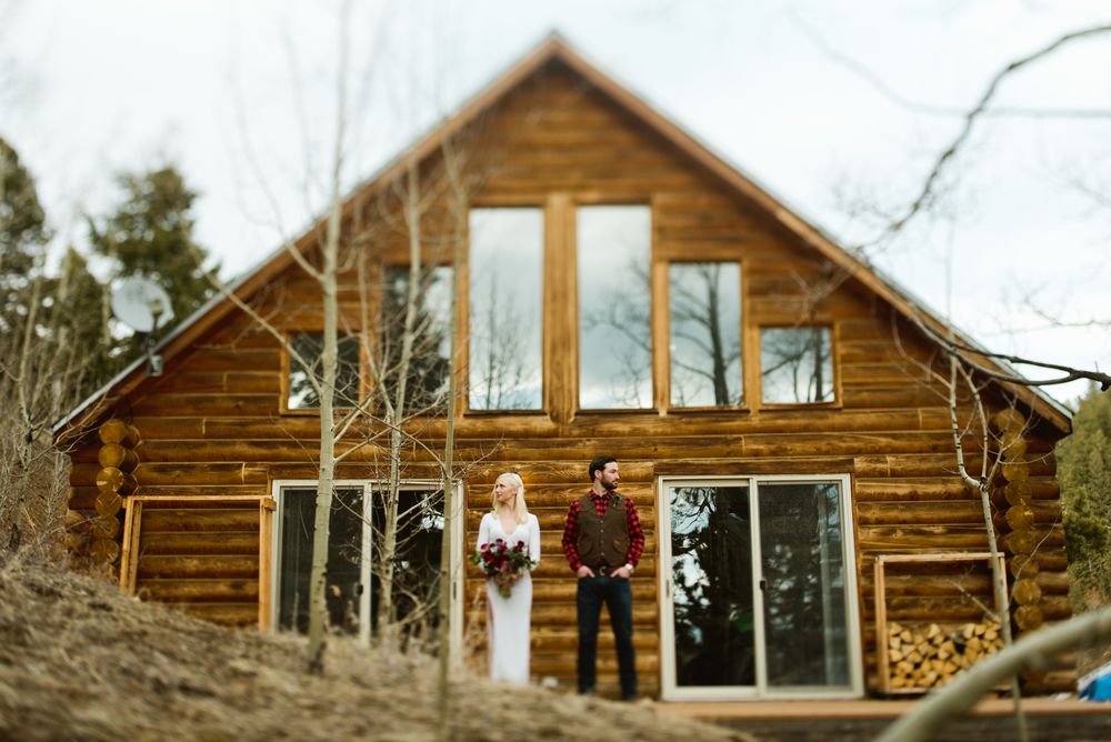 This bride and groom looking stunning in front of this mountain Lodge for their adventurous mountain elopement. Such a rustic wedding venue in Black Hawk, Colorado! | Photo by Maddie Mae