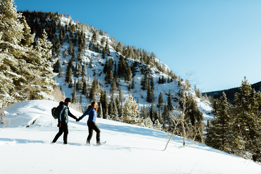 Aww such a cute snowshoeing engagement shoot in the Rocky Mountains! The sun hits the snowcapped mountains around Lost Lake so beautifully in the morning! | Rocky Mountain engagement photos by adventurous Colorado Engagement photographer, Maddie Mae.