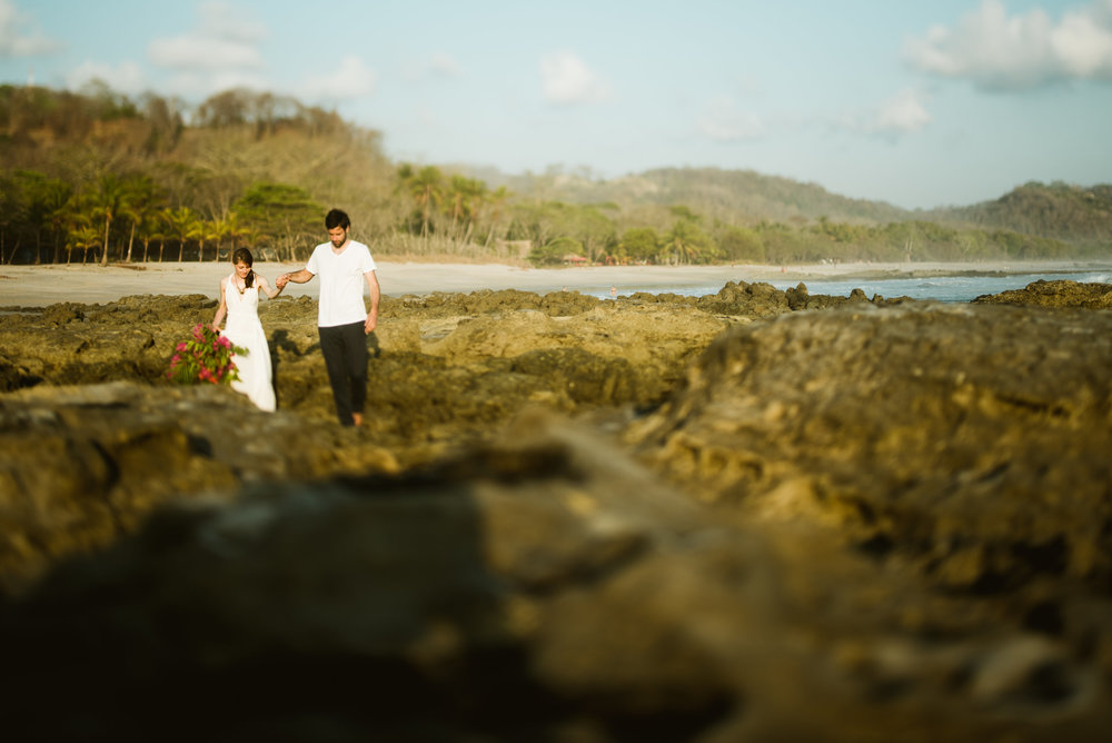 Santa Teresa Beach is absolutely breathtaking in these sunset destination elopement photos in Costa Rica. I would love to tie the knot on a rugged, rocky beach! | Beach wedding photography by destination wedding photographer, Maddie Mae.