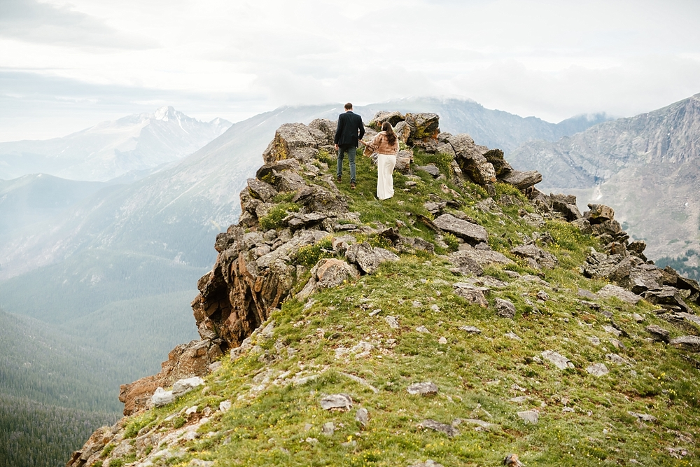 I can't believe this amazing cliffside is in Colorado! What a lucky couple to get married in such a beautiful mountain wedding location! | RMNP trail ridge road elopement photos by Colorado mountain elopement photographer, Maddie Mae.