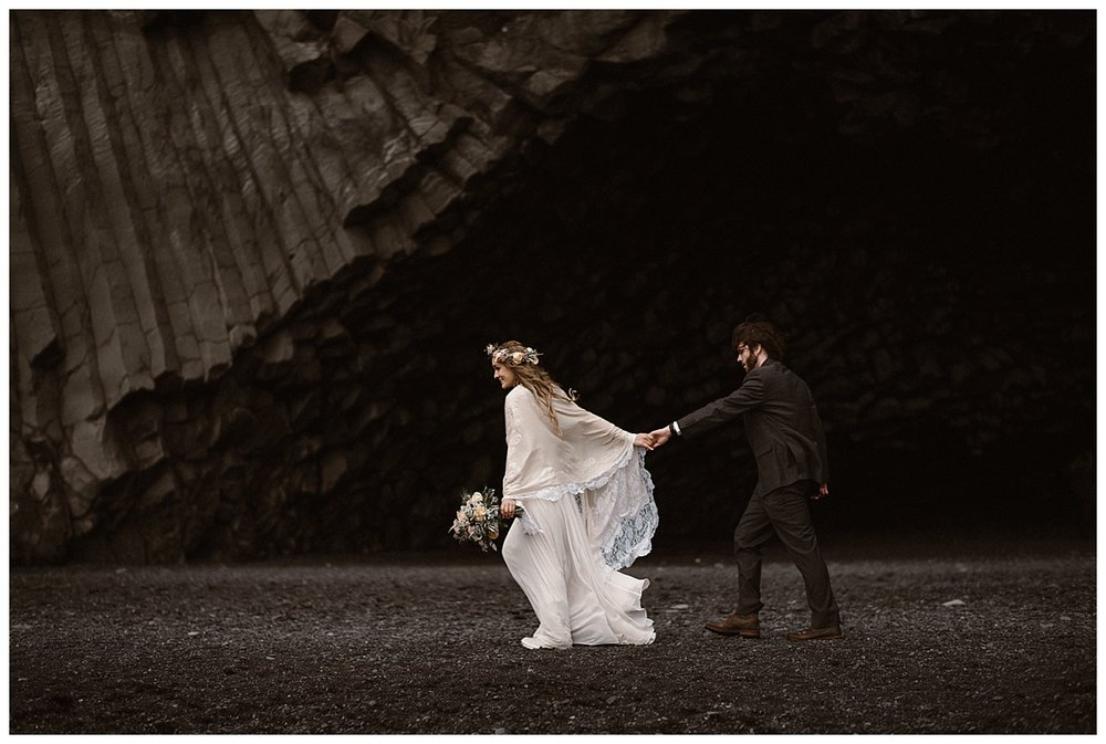 Julie grabbed Tim's hand, her white wedding dress flowing in the wind, as she lead him to the cliffs at Reynisdrangar beach at their intimate Iceland elopement. Photo of this adventurous wedding taken by traveling photographer Maddie Mae.