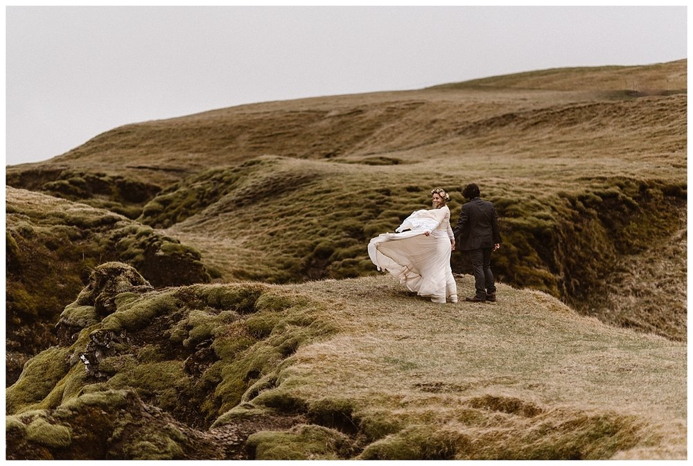 Taking a jaunt through the hills of Fjadrargljufur Canyon, Julie and Tim took a few moments for themselves, allowing the wind to catch their backs. This intimate elopement through Iceland was photographed by traveling wedding photographer Maddie Mae.