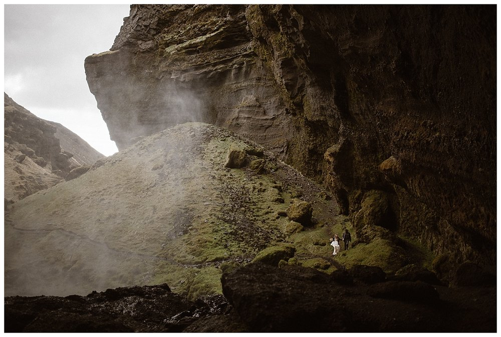 Realizing just how small they were, Julie and Tim made their way out of Kvernufoss waterfall and back up onto the grassy knolls surrounding them. Their intimate wedding photos captured by traveling wedding photographer Maddie Mae.