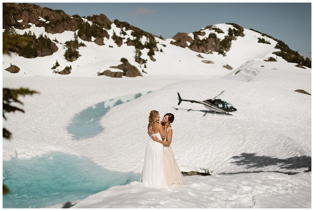 On their way back to the helicopter, Kari and Karin paused in the warm Tofino sun to share a sweet embrace above a glacial lake. This adventurous elopement captured by traveling wedding photographer Maddie Mae.