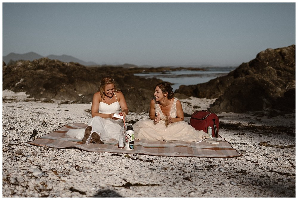 They shared sandwiches, chips and some special chocolates that Karin has specifically gotten for Kari. They enjoyed their meal in private on a deserted island in the Sound outside Tofino BC. Photos of this adventurous helicopter elopement by traveling wedding photographer Maddie Mae.