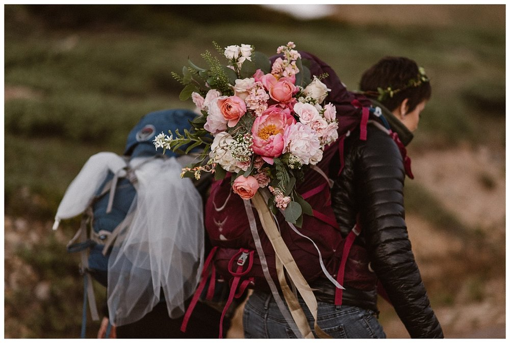 They carried their wedding gowns and oversized bouquets in their packs as they hiked up Jonas Pass with their intimate wedding photographer Maddie Mae for their sunrise elopement near Winter Park, Colorado.