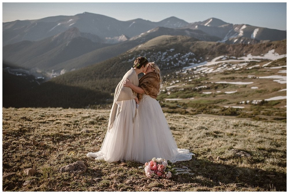 Sealing the deal with a kiss, these two brides were wed in a private elopement ceremony up Berthoud Pass in the Colorado mountains. Their sunrise wedding captured by traveling photographer Maddie Mae.