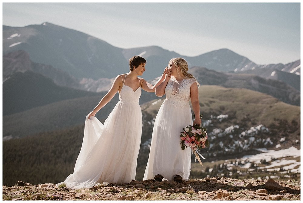 Dona grabbed Malisa's hand for the most intimate kiss as they wandered onward around Jonas Pass at their sunrise hiking elopement. Photos of their private wedding by traveling photographer Maddie Mae.
