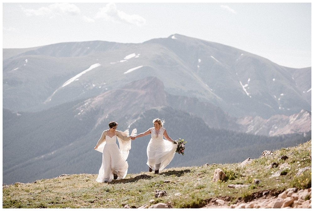 Running into the wind as the sun rose high above them and the high alpine terrain, Dona and Malisa started to make their way down Jonas Pass near Winter Park, Colorado. Photos of their intimate mountain top elopement by traveling wedding photographer Maddie Mae.