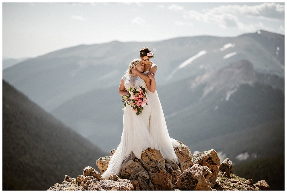 With their soft dresses tumbling down the jagged rock landscape these gorgeous brides embraced their inner mountain mermaid at their private sunrise elopement up Jonas Pass near Winter Park, Colorado. Photos by traveling wedding photographer Maddie Mae.
