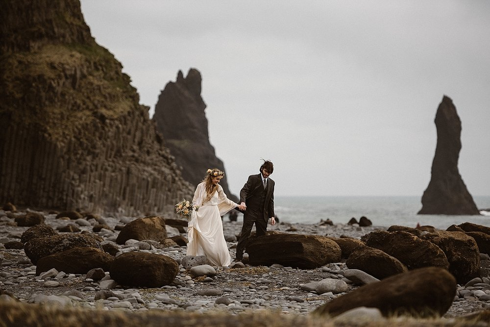 Julie and Tim walked into the wind along the Reynisdrangar beach. Their epic adventurous elopement throughout Iceland was captured by intimate wedding photographer Maddie Mae.