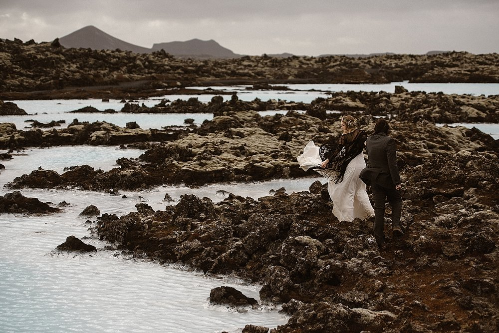 The jagged rocks of the Blue Lagoon are a stark contrast to the icy blue waters. Julie and Tim wandered around, looking for artifacts and enjoying a few quiet moments, just them and their intimate wedding photographer Maddie Mae.