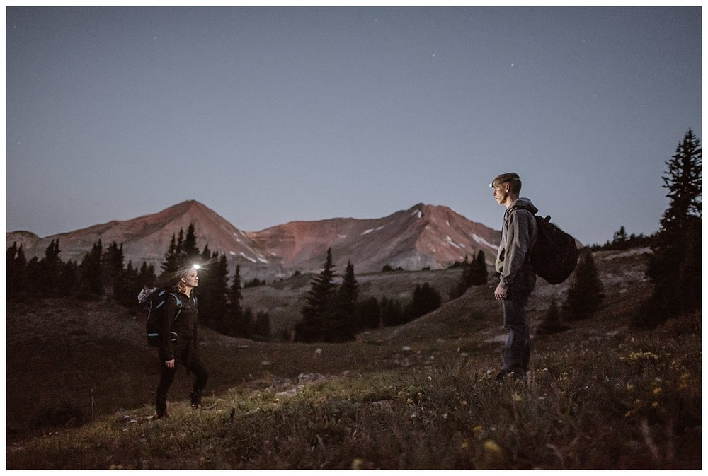 With the Crested Butte mountains glowing pink behind them, Kourtney and Gabriel paused with headlamps on to take one last look at each other in the light of dawn. This adventurous hiking elopement photographed by traveling wedding photographer Maddie Mae.