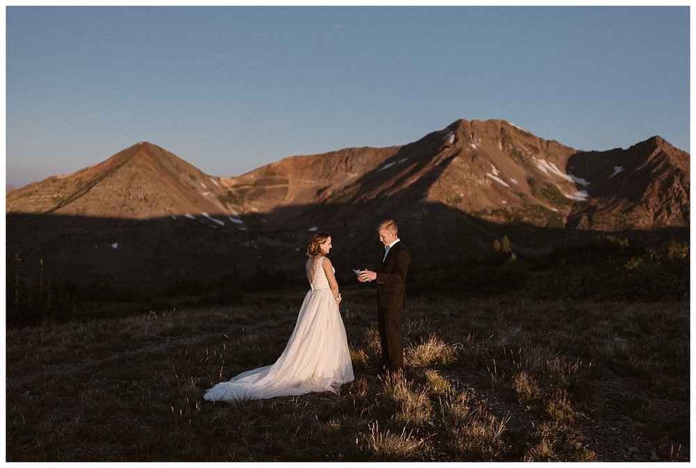 The sun crested the Colorado mountains lighting up Scarp Ridge as Gabriel began his intimate and personal elopement vows. Their private sunrise elopement outside Crested Butte captured by adventurous elopement photographer Maddie Mae.