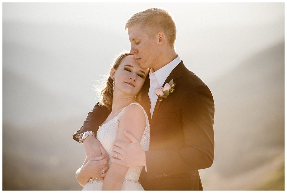 Looking like a moment from an old romantic film, Kourtney nuzzled into her husband enjoying the warmth of the sun on their skin making them glow high above the valley near Crested Butted. This intimate Scarp Ridge sunrise elopement photographed by Colorado native Maddie Mae Photography.
