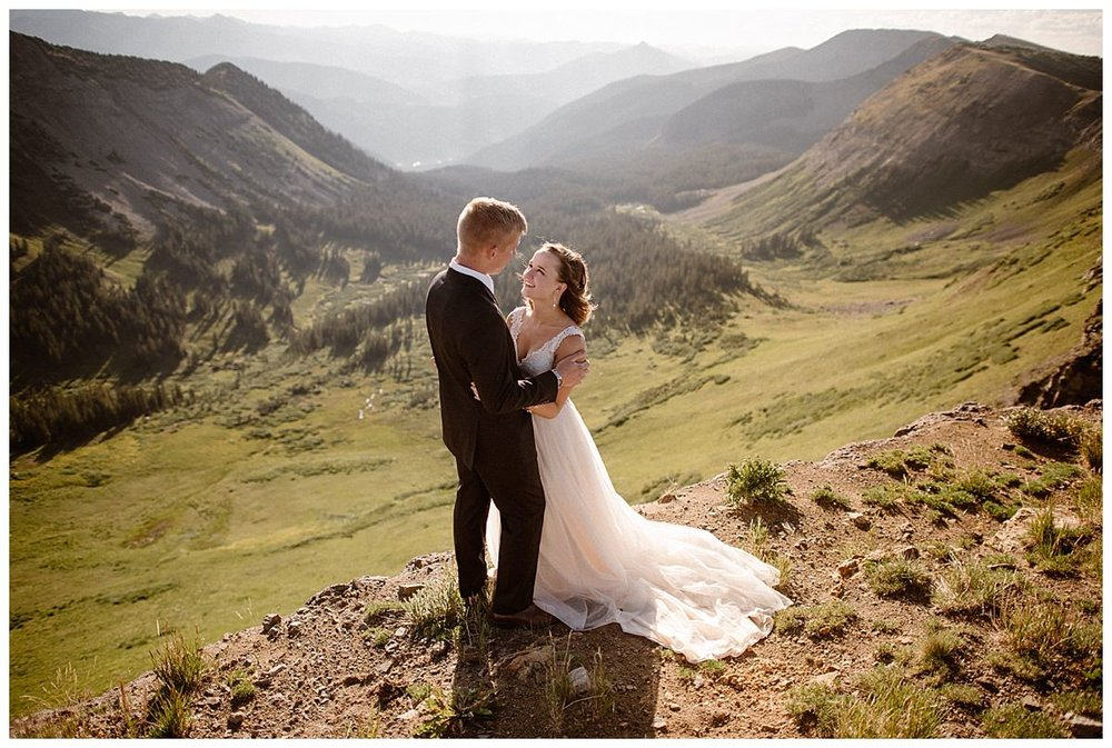 With the wind in her hair, Kourtney looked up at her smiling groom elated that they were able to celebrate their wedding the way they wanted to - with an intimate sunrise hiking elopement through the Colorado mountains near Crested Butte. Photos by Maddie Mae Photography.