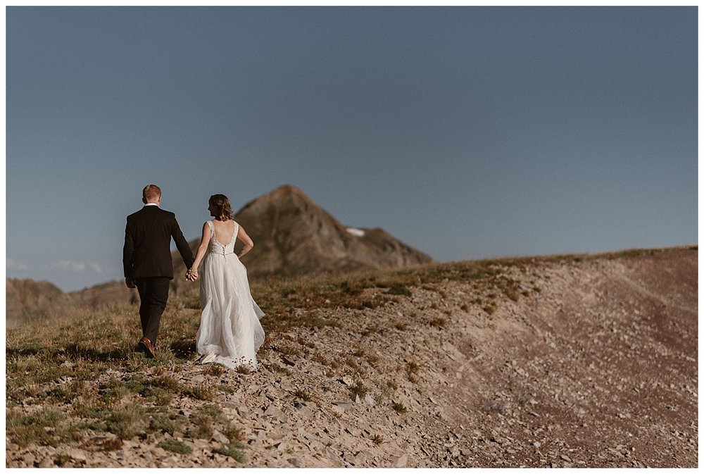 The train of her white dress dragging behind them as they hiked up the rocky ridge of the mountains near Crested Butte. This adventurous couple eloped at sunrise with only their intimate wedding photographer Maddie Mae as their witness.