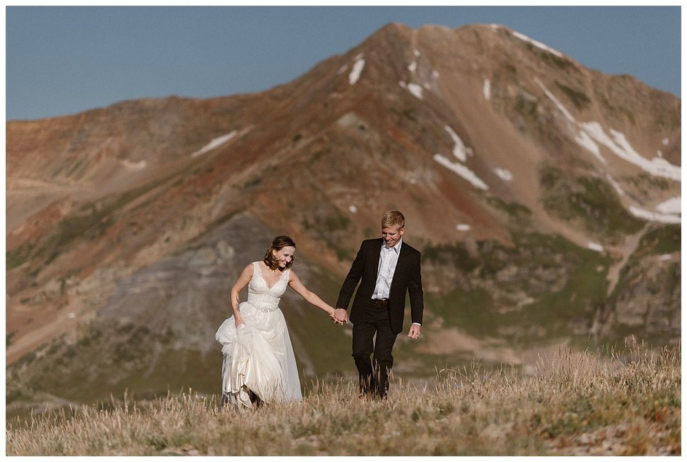 Smiling and laughing through the tall grasses of the meadow below Scarp Ridge this adventurous couple hiked on for more epic views of Crested Butte on their intimate elopement adventure through Scarp Ridge with only their wedding photographer Maddie Mae in tow.