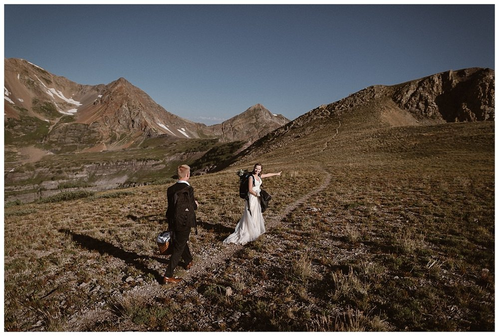 """""""Over there,"""" she pointed to the mountains ahead as they hiked on through Scarp Ridge near Crested Butte. This outdoorsy couple opted for a wedding that truly was them - a hiking elopement in the Colorado mountains. Photos of this epic private wedding by traveling wedding photographer Maddie Mae."""