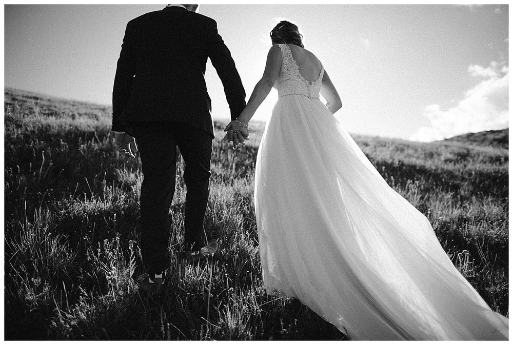 With the sun at their faces, Kourtney and Gabriel held hands as they walked through the tall meadow grass to the ridge in front of them. Photos of this intimate hiking elopement through Scarp Ridge near Crested Butte by intimate elopement photographer Maddie Mae.