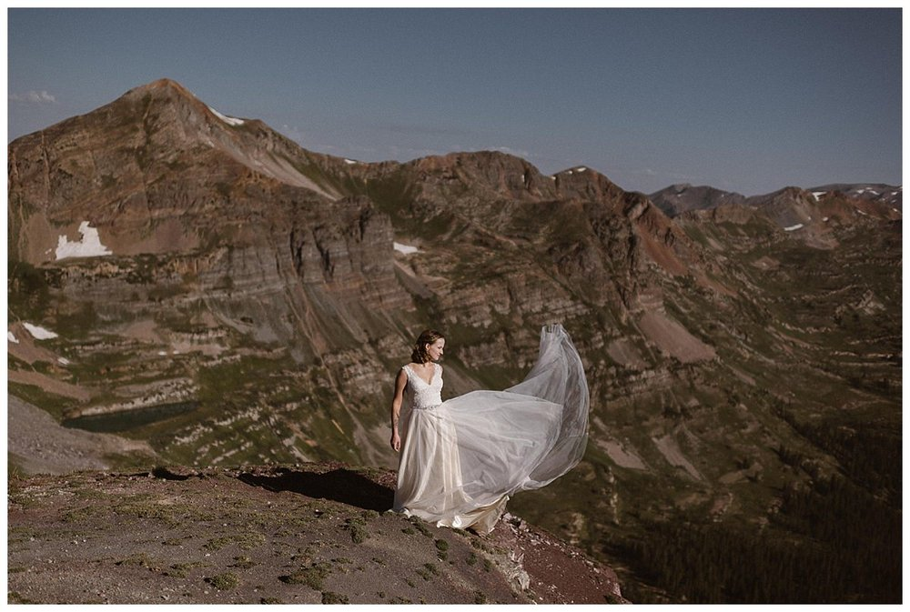The high alpine wind of Scarp Ridge caught Kourtney's vintage style flowing wedding dress making the epic landscape seem that much more grand. Photos of this adventurous elopement near Crested Butte captured by intimate wedding photographer Maddie Mae.