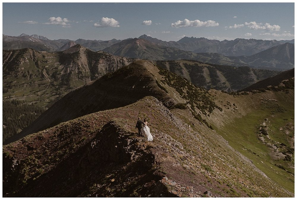 """""""Follow me!"""" Kourtney yelled as she grabbed her groom's hand and ran down the ridges of the mountains in Crested Butte. This adventurous couple opted out of tradition and eloped in a private ceremony high at sunrise on Scarp Ridge. Photos of their epic hiking elopement by traveling wedding photographer Maddie Mae."""