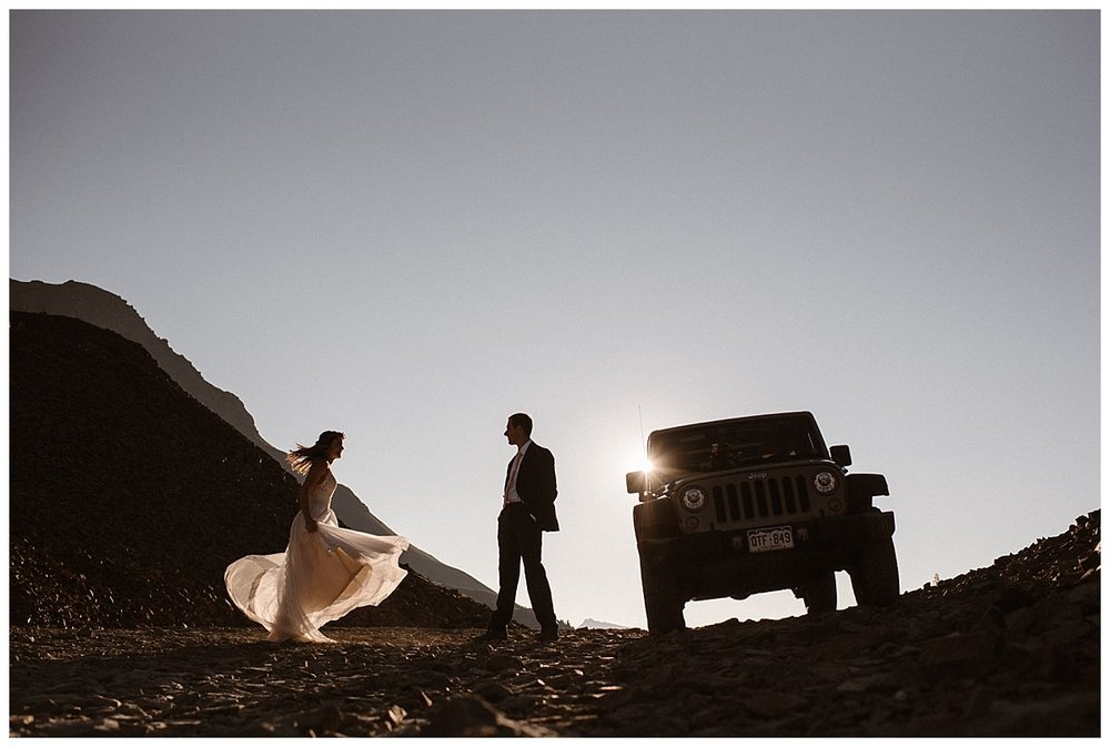 The wind caught Joys white wedding dress as she spun around to get back to the Jeep 4x4 where Clint was waiting, ready to open the door for her. The sun rising quickly in the sky after their intimate sunrise first look up Ophir Pass in the San Juan Mountains with only their intimate wedding photographer Maddie Mae.