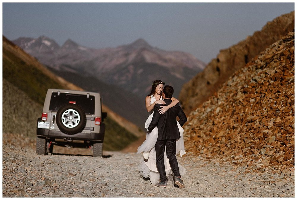 Before hopping back in their Jeep 4x4 and continuing down Ophir Pass, Joy quickly turned back and playfully jumped in her grooms arms. Photos of this romantic sunrise first look in the San Juan Mountains overlooking Telluride by adventurous elopement photographer Maddie Mae.