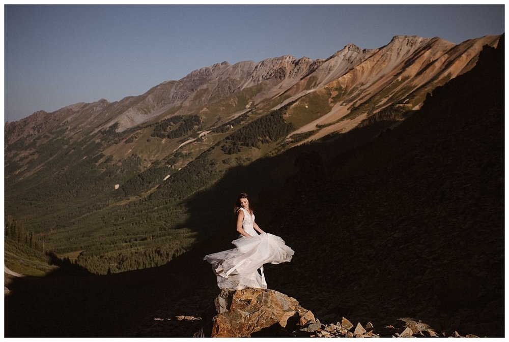 Clint pulled the Jeep over,so Joy could jump out and twirl in her flowing white wedding dress high in the San Juan Mountains. Photos of this private first look and intimate wedding at the Telluride Ski Resort by intimate elopement photographer Maddie Mae.
