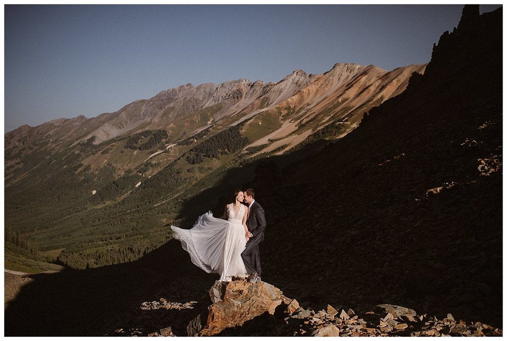 The wind caught Joy's flowing white wedding dress making her look like an angel on a mountain top with her handsome groom by her side. These epic bridal portraits in the San Juan Mountains near Ophir Pass taken by intimate elopement photographer and Colorado native, Maddie Mae Photography.