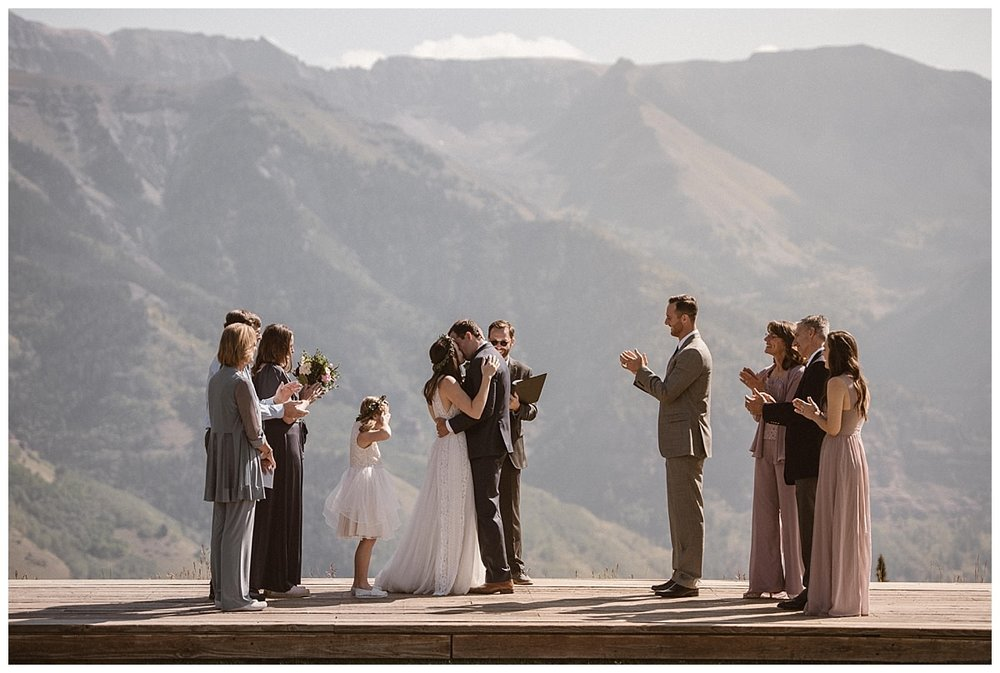 "With an ""I do!"" they were wed and leaned in for their first kiss as husband and with with the San Juan Mountains as their backdrop at the Telluride Ski Resort with their closest friends and family looking on. Photos of this adventurous Ophir Pass first look and intimate wedding in Telluride by traveling elopement photographer Maddie Mae."