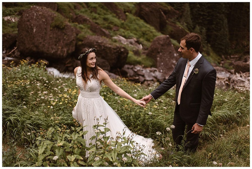 Joy took her husbands hand and lead him through the tall grass at Bridal Veil Falls where they had snuck off to after their intimate wedding ceremony at Telluride Ski Resort for some private bridal portraits with only their traveling wedding photographer Maddie Mae.