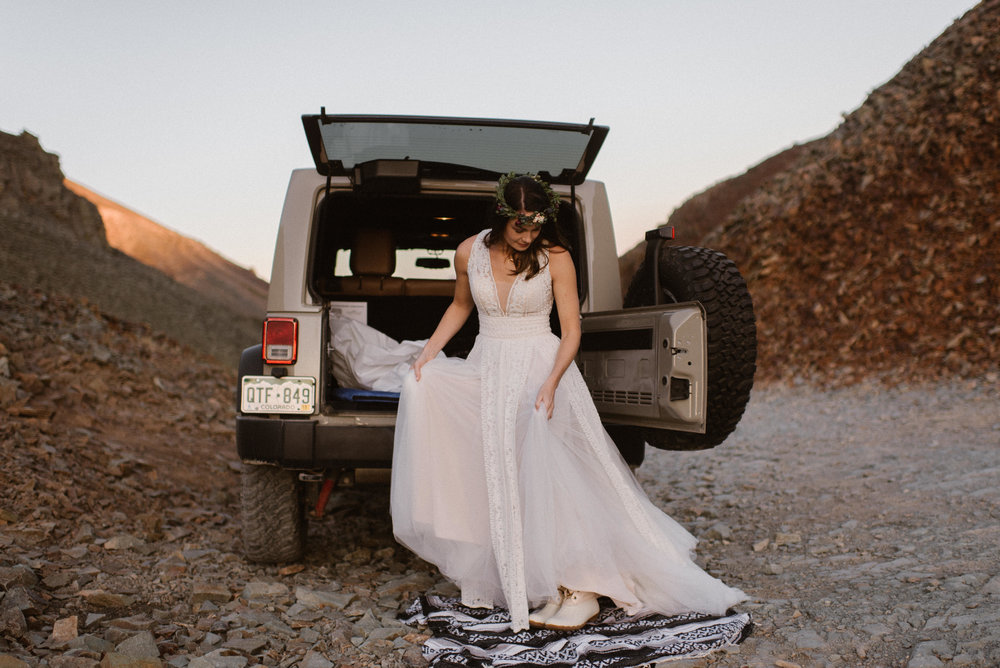 Joy looked like vintage perfection in her flowing white lace and tulle wedding dress. She wore a delicate flower crown and white hiking boots to top off her mountain bride look. Photos of this adventurous Jeep 4x4 wedding in Telluride by intimate wedding photographer Maddie Mae.