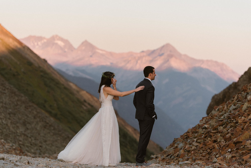 With the alpine glow on the San Juan Mountains behind them, Joy tapped her groom on his shoulder for their private first look above Telluride. Photos of this adventurous couple's intimate wedding by traveling elopement photographer Maddie Mae.