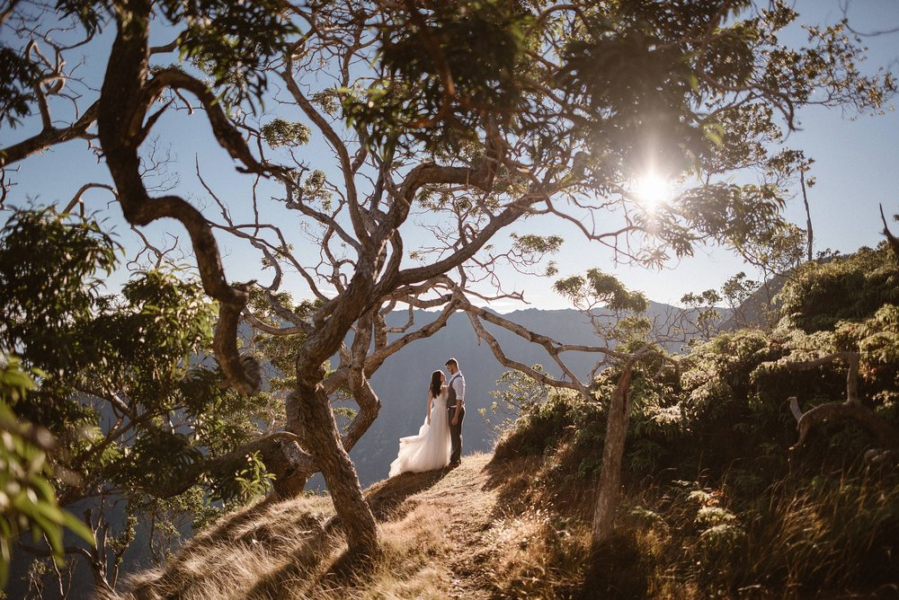 The Hawaiian sun high in the sky lighting up this romantic adventurous couple. The twisted trees of Kokee State Park framing them perfectly as they meandered their way to the perfect location for their intimate elopement ceremony. Photos of this epic Kauai hiking elopement by traveling wedding photographer Maddie Mae.