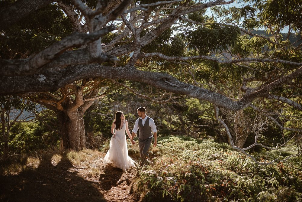 Deep in conversation, as though no one was around, Kourtney and Chris made their way through Kalalau Valley where the ferns at their sides were a mess of shaggy greenery and the twisted trees looking perfect to climb. Photos of this intimate Kauai hiking elopement by traveling wedding photographer Maddie Mae.