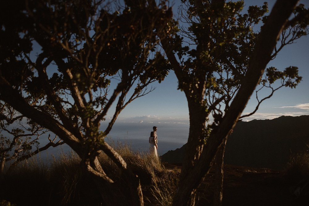 The sun hung low in the afternoon sky as Kourtney and Chris said their vows at Kokee State Park on Kauai. Their adventurous Hawaiian elopement avoided the touristy beaches and instead they chose to hike to Kalalau Lookout with their intimate traveling wedding photographer Maddie Mae.