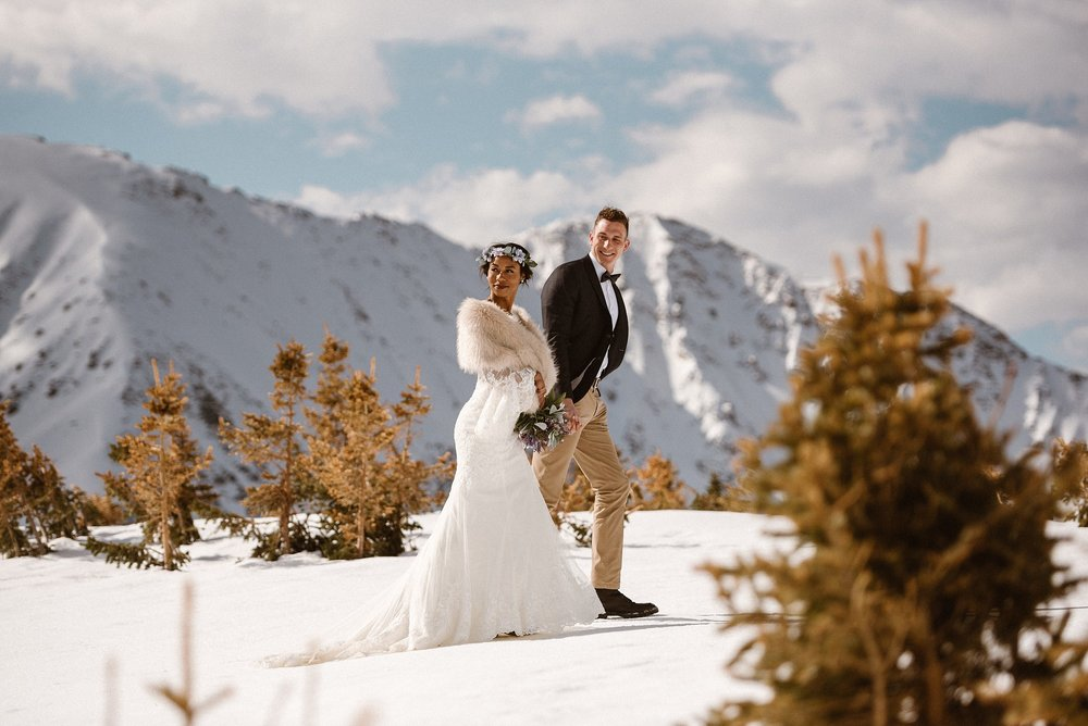 With the wind softly blowing up Loveland Pass, this stunning vintage couple shared a sweet snuggle. The glowing white Rocky Mountains set the backdrop for this intimate elopement captured by traveling wedding photographer, Maddie Mae.