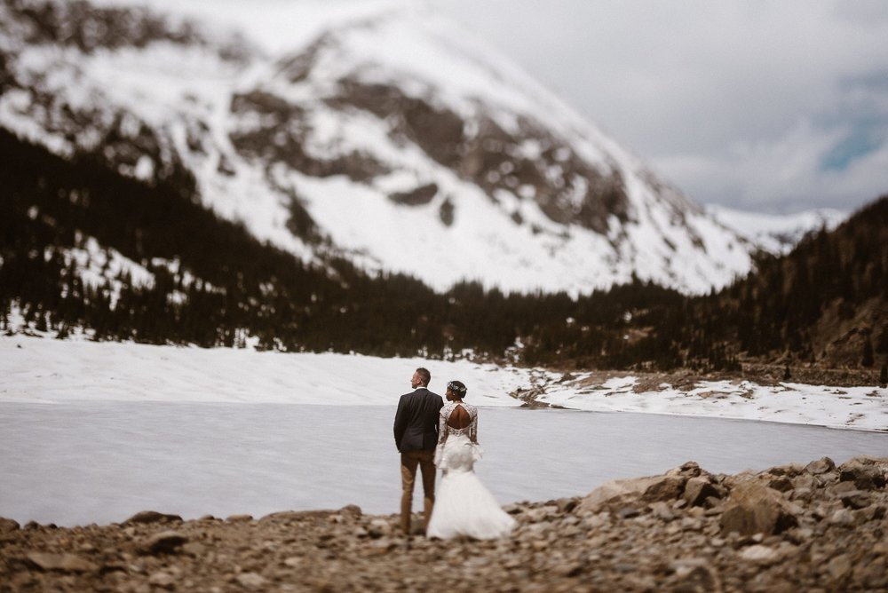 Walking along the rocky shores of Montgomery Reservoir, Jared grabbed his bride, squeezing her tightly in the bright afternoon sunshine. Intimate elopement photography by traveling wedding photographer Maddie Mae.