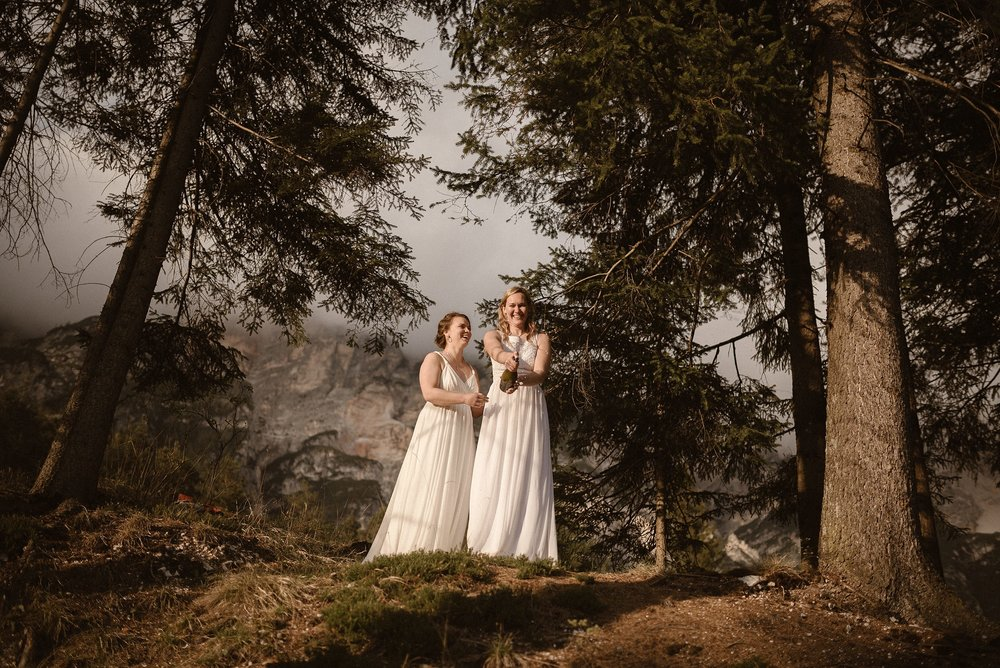 No wedding is complete until a bottle of champagne is popped! These gorgeous brides in the forests near Lake Braise in Northern Italy for their intimate elopement. Captured by Maddie Mae Photography.