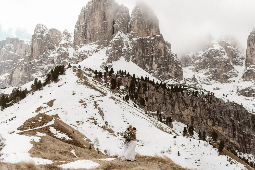 Pausing to enjoy the company as the high alpine Dolomite wind rushed around them. These stunning brides radiated love far beyond the Northern Italian mountainside where they were about to celebrate their intimate elopement. Captured by Maddie Mae Photography.