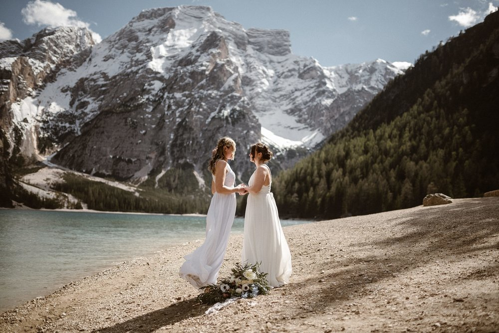 With no one in sight, they put down their oversized bouquet and began their intimate elopement ceremony with only their adventurous wedding photographer as their witness. This Dolomite mountain elopement captured by Maddie Mae Photography.