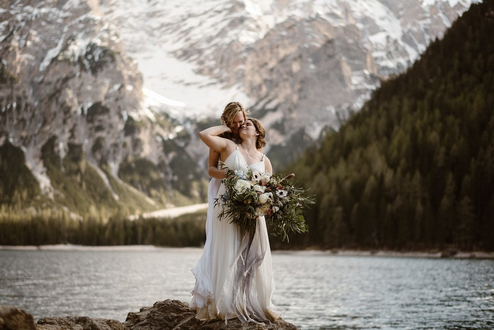 These stunning brides smiled and snuggled next to the Italian lake where they had just said their intimate elopement vows at the foothills of the Dolomites. Photos of this epic romantic destination elopement by traveling wedding photographer Maddie Mae.
