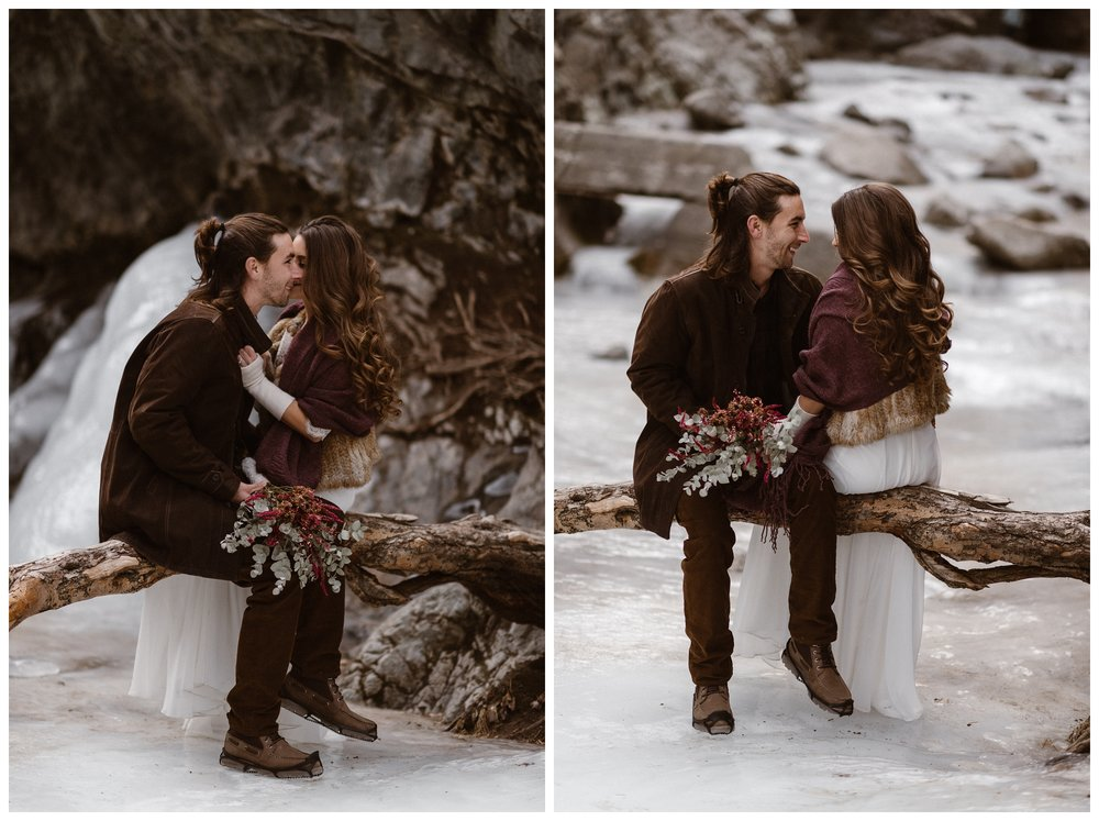 Olivia and Justin sit on a log outside Zapata Falls, frozen in ice, during their winter elopement. Photo by Maddie Mae Photo, Adventures Instead.