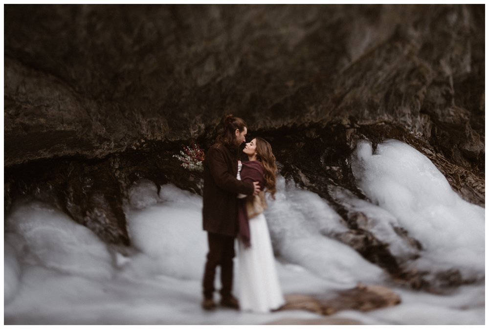 Olivia and Justin on the frozen Zapata Falls outside Great Sand Dunes National Park in Southern Colorado during their winter adventure elopement wedding. Photo by Maddie Mae Photo, Adventures Instead.