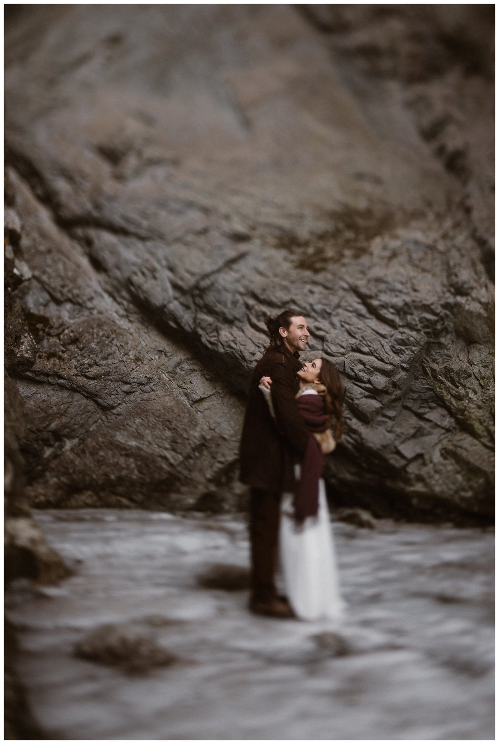 Olivia and Justin stand surrounded by ice at the frozen Zapata Falls outside Great Sand Dunes National Park for their winter elopement. Photo by Maddie Mae Photo, Adventures Instead.