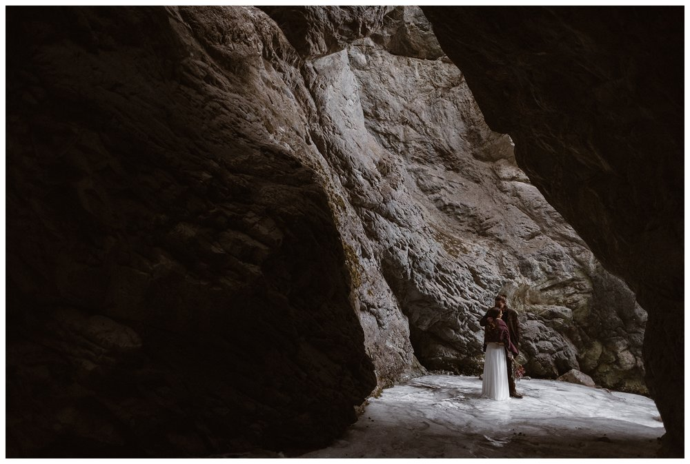 Zapata Falls forms a natural ice cave around Olivia and Justin during their winter wedding elopement in Southern Colorado. Photo by Maddie Mae Photo, Adventures Instead.